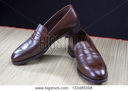 Mens Footwear Concepts. Pair of Stylish Brown Penny Loafer Shoes Placed on Straw Surface against Black.Horizontal Image