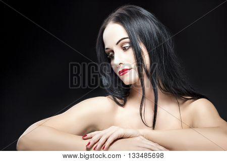 Beauty Concepts and Ideas. Sensual Caucasian Brunette Woman With Naked Shoulders and Silk Skin Posing Against Black Background. Horizontal Shot