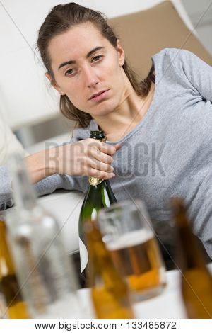 drunk girl holding bottle of alcohol