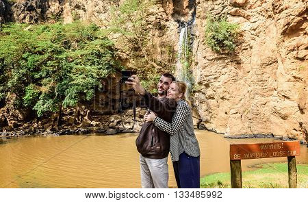 Kenya, Africa - March 9, 2016: Young couple taking a selfie with camera by Waterfall in Kenya