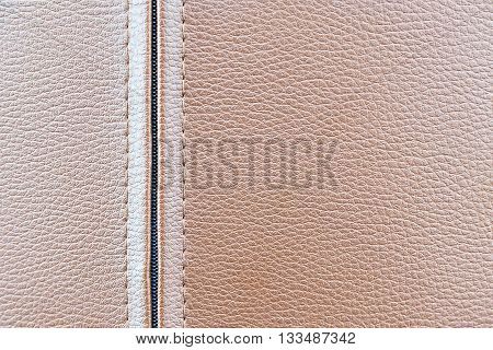 the leather texture background in the light brown tone with the zipper. Closeup