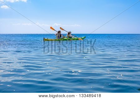MELOS GREECE - SEPTEMBER 4 2012: Man and woman kayaking in calm Aegean Sea waters.