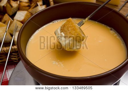 Сheese fondue - piece of bread (croutons) in a liquid cheese