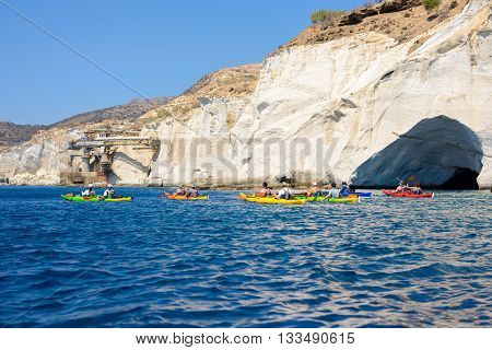 MELOS GREECE - SEPTEMBER 4 2012: People with kayaks exploring the south coast of Melos island near the Xilokeratia pozzolan quarry staith.