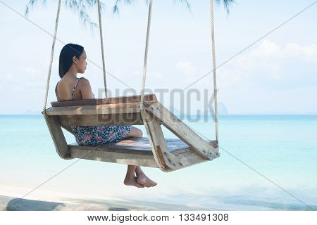 Woman Sitting On Rope Swing On Paradise Beach.