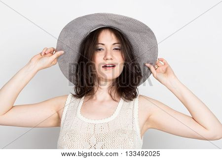 beautiful young brunette woman holding a broad-brimmed hat. girl flirting concept. expression of different emotions.