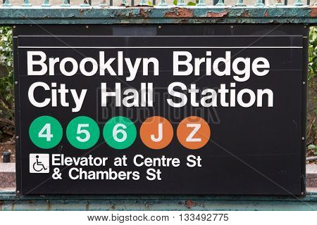 NEW YORK CITY - CIRCA 2016: Brooklyn Bridge City Hall subway station sign hangs above the underground entrance in lower Manhattan, New York City in 2016. The NYC subway system provides access to Manhattan, Queens, Brooklyn, the Bronx, and Staten Island.