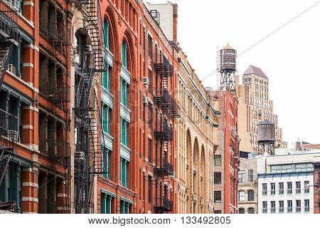 Block of buildings with fire escapes and water towers in Soho Manhattan New York City