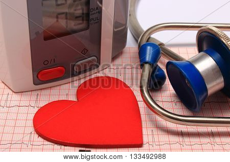 Medical stethoscope instrument for measuring blood pressure and red heart shape on electrocardiogram graph ekg heart rhythm medicine concept