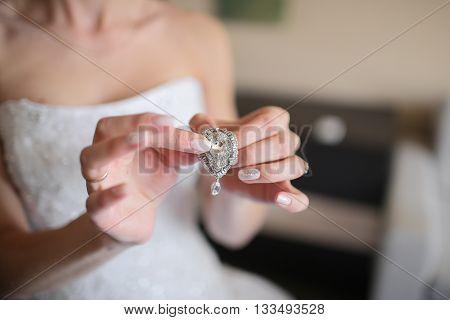 Wedding earrings on a female hand, she takes the earrings, white dress