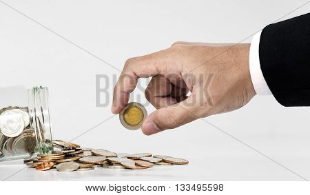 Hand picking up coin from spilled from glass jar