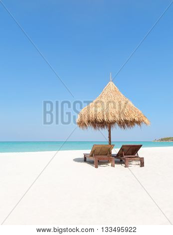 Wooden Deckchairs And Straw Parasol On Paradise Beach.