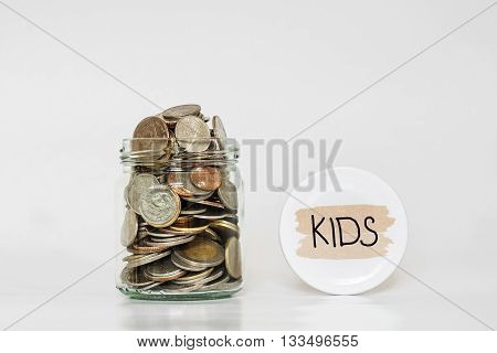 Coins in glass jar, saving money for their Kids