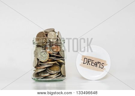 Coins in glass jar, saving money for following Dreams