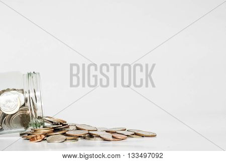 Coins spilled from glass jar, with copy space on white background