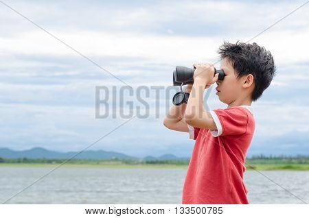 Young Asian boy using binoculars at camp
