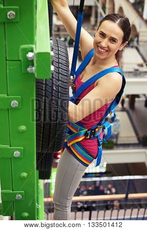 Sportswoman in safety equipment is climbing on the wall in indoor rock-climbing sport center