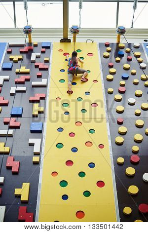 Young woman in safety harness has almost reached the top of the climbing wall in indoor rock-climbing center