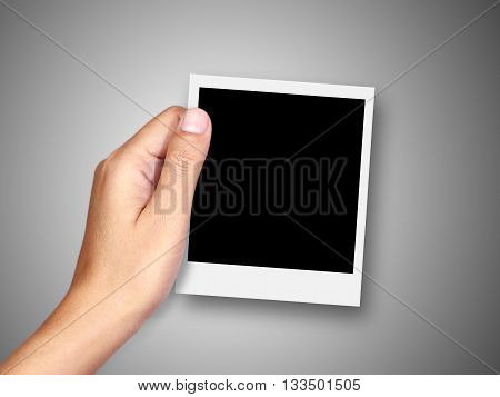 Hand holding blank instant photo frame on background