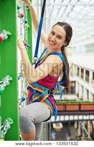Sportswoman in safety equipment is smiling while climbing on the wall with chains in indoor rock-climbing center