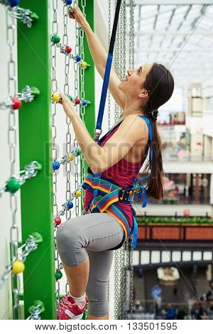 Sportswoman in safety equipment is climbing on the wall with chains in indoor rock-climbing center