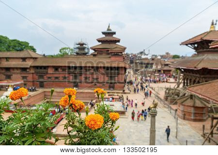 Patan Durbar Square in Nepal. Focus on marigolds, people and building out of focus.