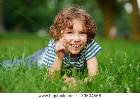 The boy of 8-9 years lies in a dense green grass. The boy has curly hair a turned-up nose chubby lips and blue eyes.He has in a hand a small floret. The boy looks in a camera and smiles.