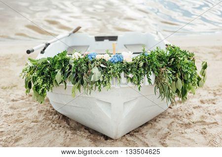 lonely white boat on the bank of the river decorated with flowers