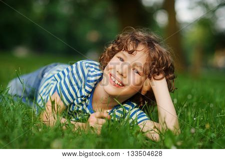 The boy lies in a green grass having propped up the head a hand. He looks in a camera and smiles. The boy has curly hair and a nice face.