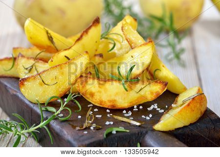 Baked potato wedges with rosemary served on a shabby cutting board with potatoes in the background