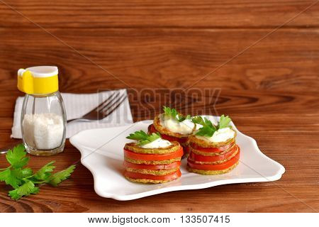 Appetizer consisting of fried zucchini, fresh tomatoes, yogurt and parsley. Chopped and fried in vegetable oil zucchini. Fresh sliced tomatoes. Zucchini appetizer on a plate. Napkin, salt shaker, fork