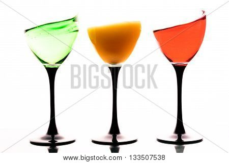 Three Wine Glasses With Colored Liquids On A White Background