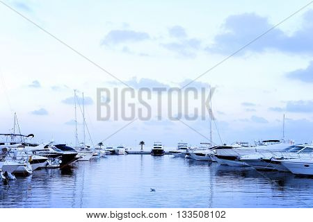 Yacht harbor after the sunset, blue hour. Pastell colored light and anchored boats, quiet scene.