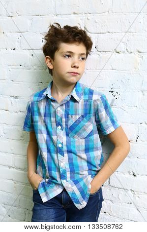preteen handsome boy in checked blue shirt close up portrait on white brick wall background