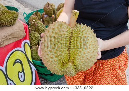 Hand holding durian in the market .