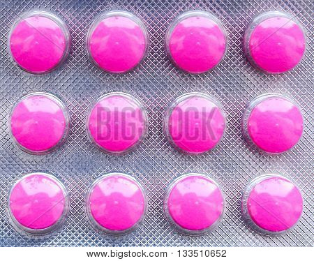 Closeup of blister pack with pink pain pills.