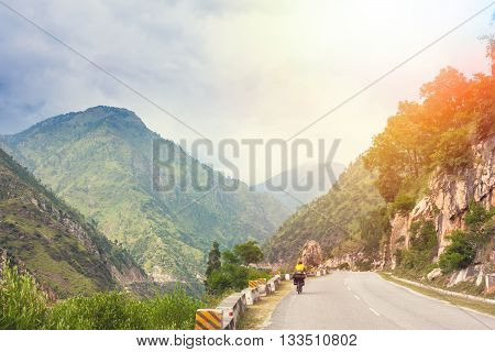 Himalayas landscape with two cyclist, mountains, road, river and clouds. Jammu and Kashmir State, North India