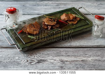 Tray with cooked meat. Meat and small pepper. Spicy veal medallions with herbs. Jars filled with dry ice.