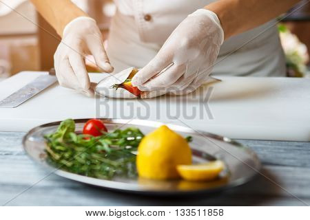 Hands put lemon into fish. Fish on white cooking board. Chef stuffs fish with lemon. Preparing a healthy seafood dish.