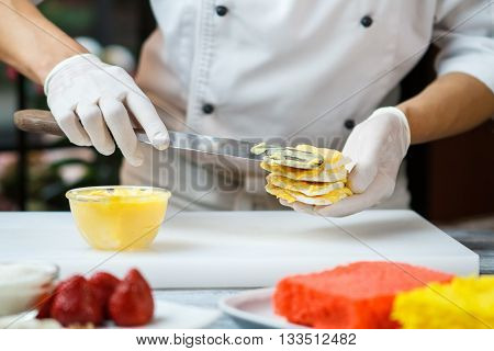 Hand with spatula applying custard. Bowl on white cooking board. Pastry chef prepares dessert. Sweet filling and crispy dough.