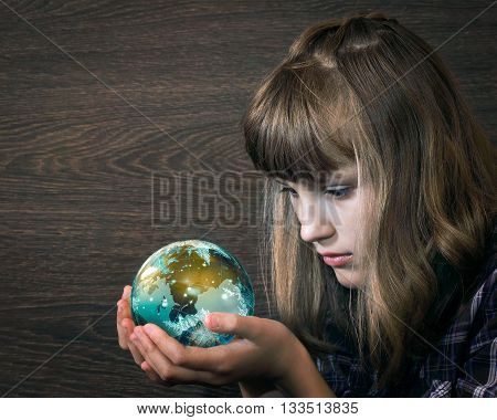 Girl looks at a glass ball in his hands. The concepts and ideas - the planet earth, magic, watch, study. Ecology, Clean Planet