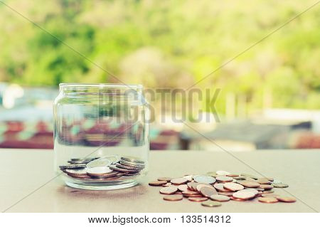 Close up of glass bottle stacking silver coins on wooden table