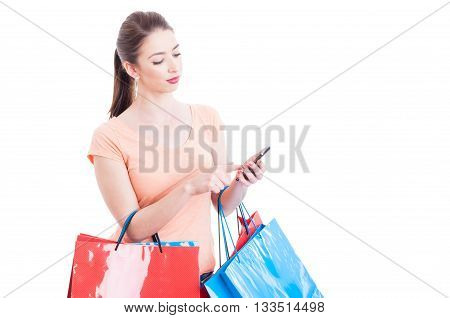 Female Holding Shopping Bags Checking Online Banking On Mobile