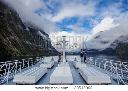 MILFORDSOUND NEW ZEALAND-AUGUST 30 : tourist on roof of milfordsound cruise with high mountain background on august 30 2015 in Milford Sound fiordland national park New Zealand