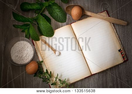 old kitchen recipe book with wooden ladle and eggs over wood