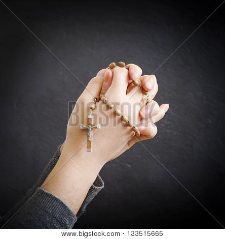 female hands with rosary over dark background
