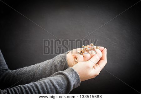 Female Hand With Rosary In Daylight