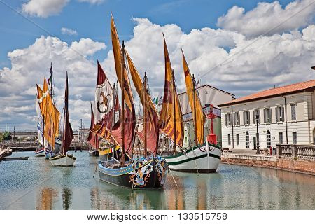the port canal of Cesenatico seaside town in Emilia Romagna Italy where ancient fishing sailing boats of the Adriatic sea are displayed in the canal
