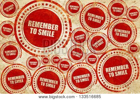 remember to smile, red stamp on a grunge paper texture