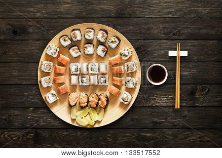 Japanese food restaurant, sushi maki gunkan roll plate or platter set. Chopsticks, ginger and wasabi. Sushi at bamboo round plate, rustic wood background. Top view with soy sauce